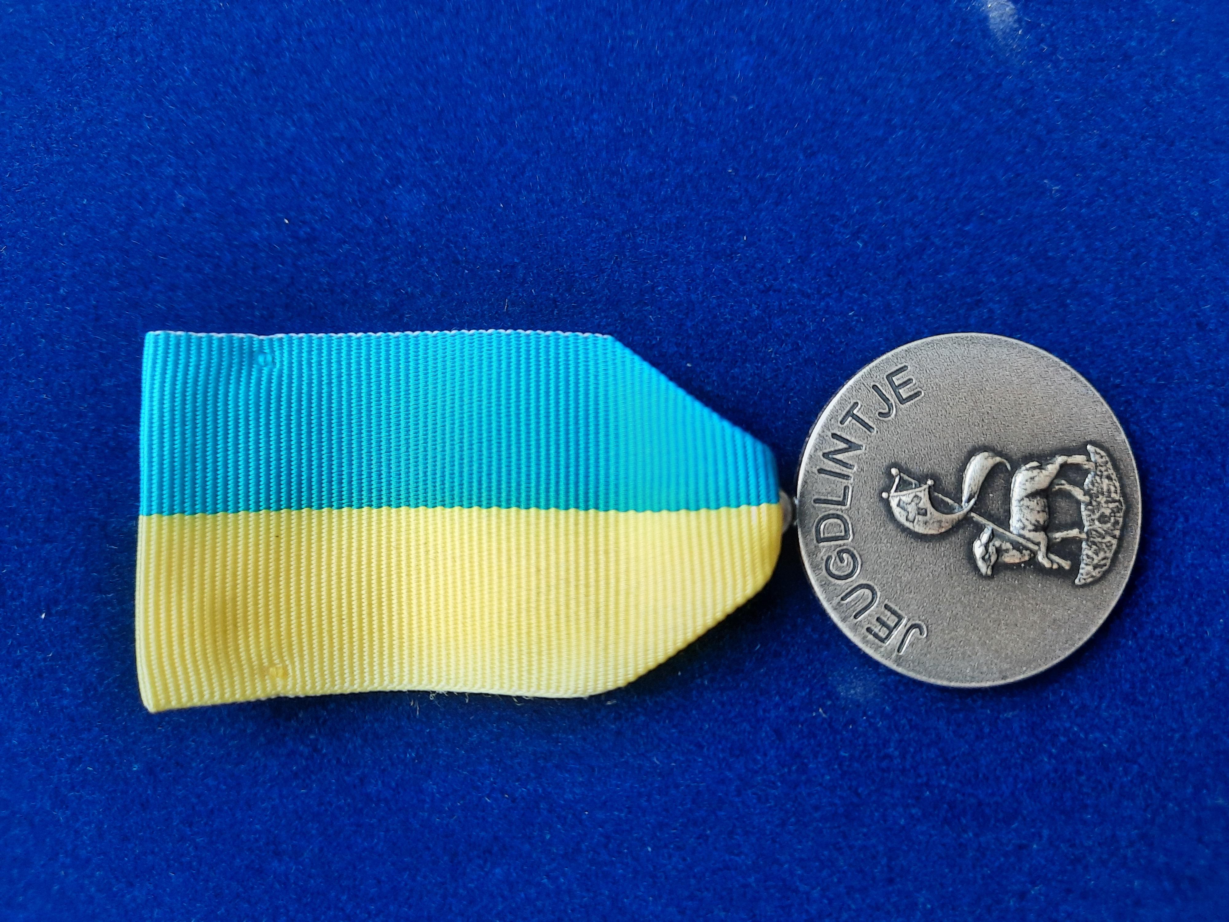 Voorbeeld van het jeugdlintje - voorkant. Geel met blauw lint, met op de munt het lams god afgebeeld